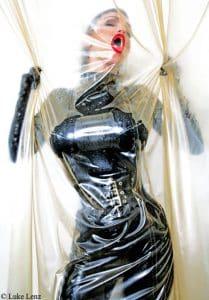 Latex Lady, Frau in Latex-Catsuit hinter Latex-Vorhang